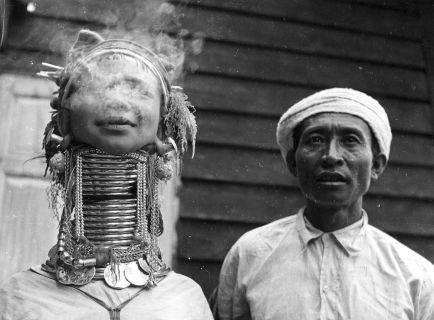 circa 1955: A Padaung, or Kayan, woman exhales smoke. Originally a Mongolian tribe, the Padaung have been assimilated into the Karen group native to Mayanmar (Burma). A stiking feature of Padaung culture is the fitting of brass rings to the necks and limbs of women born on Wednesdays. From the age of five or six, successive rings are fitted every two years, denoting the status of their family. (Photo by Three Lions/Getty Images)