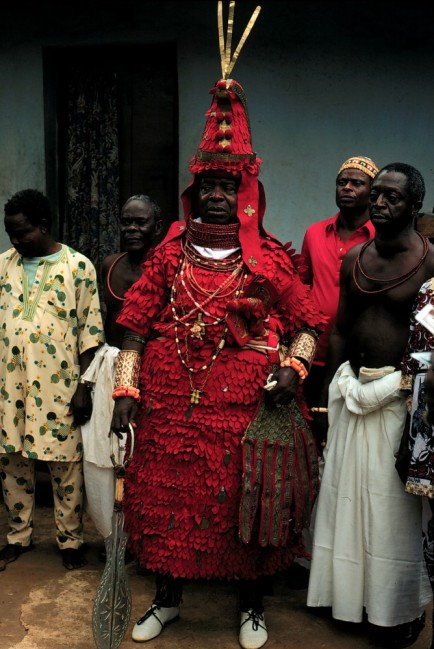 Here one of the highest ranking Eghaevbo n'Ore (town chiefs) is seen wearing the ododo cloth armor that has been depicted for centuries in brass and ivory, because the color scarlet embodies power to over come hostile forces, this bright red