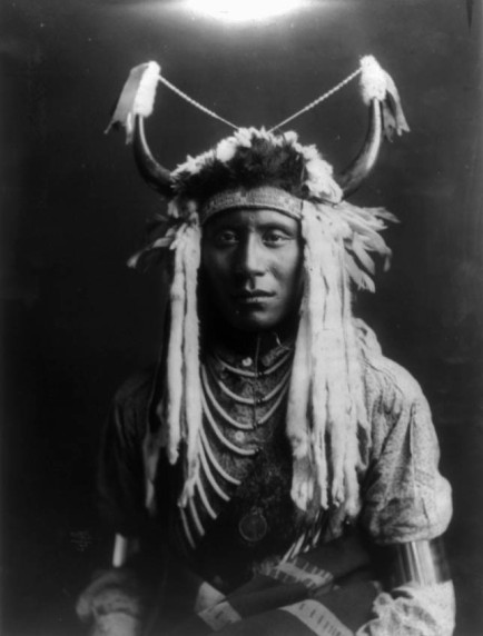 Curtis, Edward S., 1868-1952, photographer Date Created/Published: c1900. Medium: 1 photographic print. Summary: Half-length portrait of a Native man, wearing headdress, facing front.